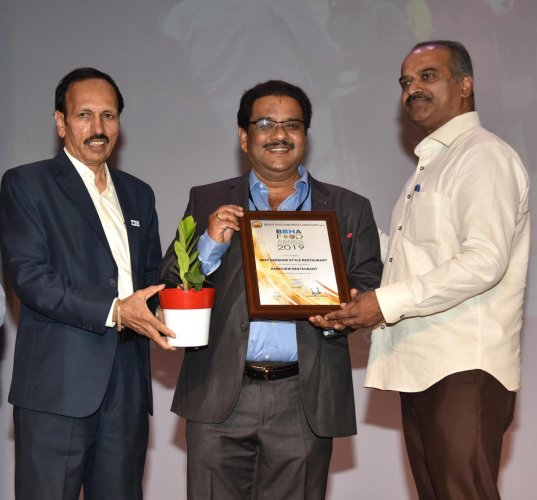 Bangalore Central parliamentarian P C Mohan presents the 'Best Darshini' award to Narasimhamurthy of Parkview Hotel at an awards ceremony hosted by the Bruhat Bangalore Hotel Association (BBHA) on Saturday. BBHA Chairman P C Road is present. DH PHOTO/MANJ
