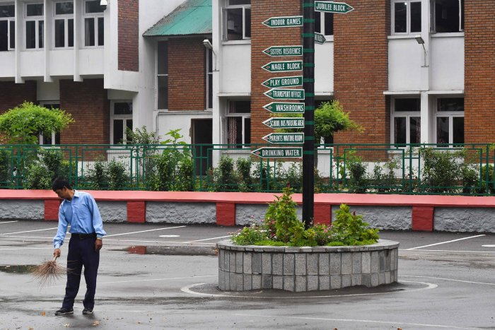 A worker cleans the campus of an empty school in Srinagar. (AFP Photo)