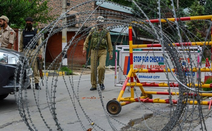 Police personnel block the road near the residences of former chief ministers Omar Abdullah and Mehbooba Mufti during curfew like restrictions on the 13th consecutive day, following the abrogation of the provisions Article 370 in Jammu and Kashmir, in Srinagar. (PTI Photo)