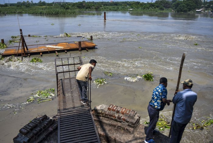Officials check the water level of Yamuna river as it rises after the release of water from Hathnikund Barrage, in New Delhi. (PTI Photo)