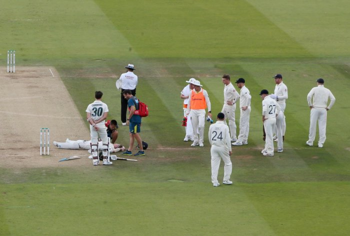 Australia's Steve Smith receives treatment as he lays on the floor after being hit by a ball from England's Jofra Archer as Australia's Pat Cummins and England players look on. (Reuters Photo)
