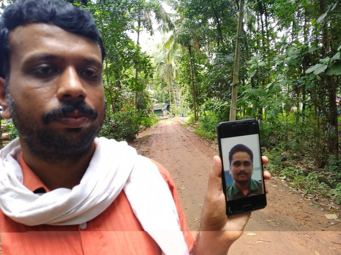 Aneesh's cousin, Dileep shows his photo on the phone (DH Photo)