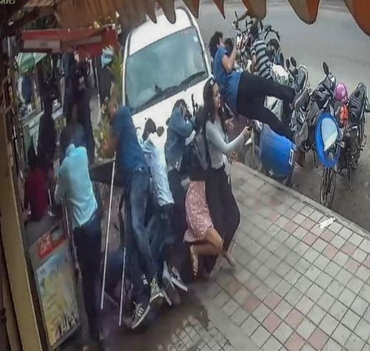 A video grab shows the car climbing the footpath and flinging people in HSR Layout on Sunday.