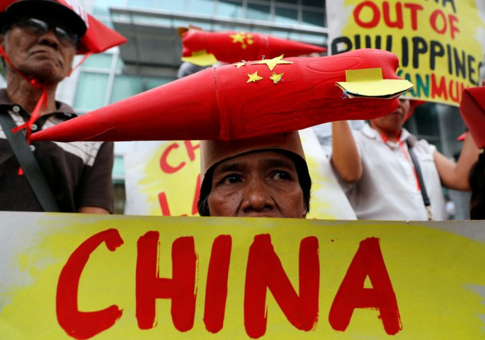 Protestors display placards during a rally by leftwing activists outside the Chinese Consulate, to protest Beijing's continued reclamation activities in the South China Sea, in Makati, Metro Manila in the Philippines February 10, 2018. REUTERS/Erik De Cas