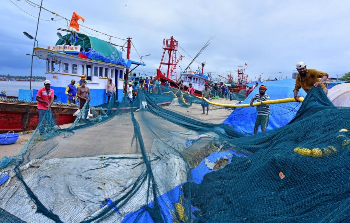 Labourers of a purse seine fishing boat make preparations to go on deep-sea fishing, at Old Port in Mangaluru on Monday. DH Photo / Govindraj Javali