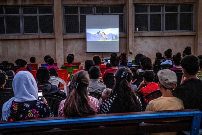 """Children attend a film screening as part of the mobile cinema """"Komina Film"""" initiative organised by Syrian-Kurdish filmmaker Shero Hinde. (AFP file photo)"""