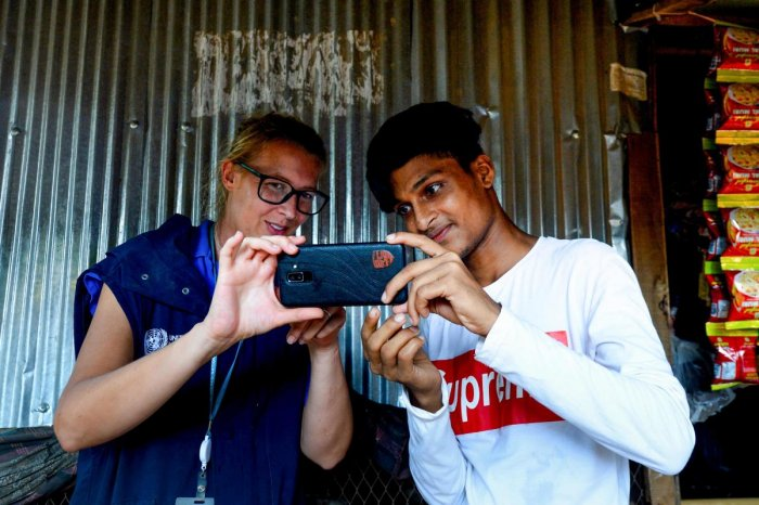 Rohingya youth Mohammad Rafiq on methods to take better photos with his mobile phone at the Kutupalong refugee camp. (AFP Photo)