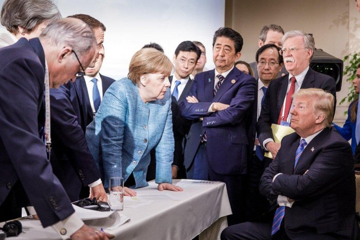 US President Donald Trump talks with German Chancellor Angela Merkel surrounded by other leaders during the G7 Summit in La Malbaie, Quebec, Canada. (AFP File Photo)