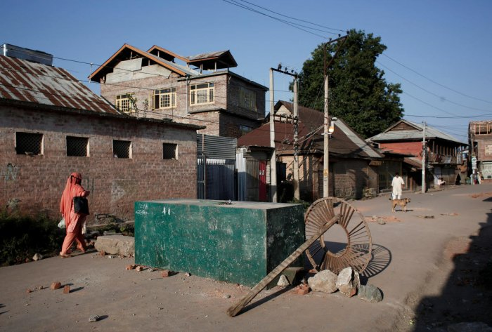 A Kashmiri woman walks past a blockade put up by residents to prevent security forces from entering their neighborhood during restrictions, in Srinagar. (Reuters Photo)
