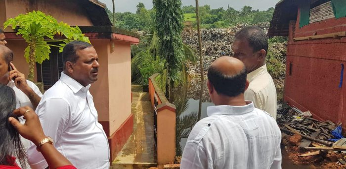 Former minister U T Khader and others visit areas at Pacchanady affected with the sliding of garbage on Wednesday.
