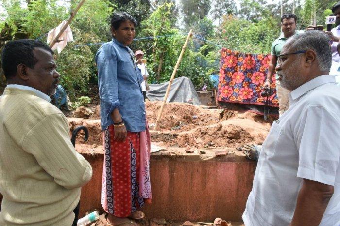Minister S Suresh Kumar speaks to a flood victim in Kumbaragudi near Siddapura.