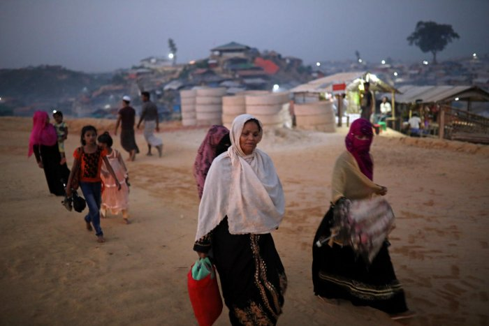 Rohingya refugees walk along the road in the evening at Balukhali camp in Cox's Bazar, Bangladesh. Reuters File Photo