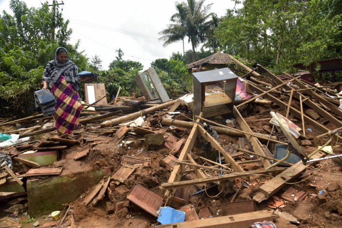 P M Jameela tries to salvage belongings from the debris of her house which was ruined in rain at Bethri village in Virajpet taluk of Kodagu district. (DH Photo/B H Shivakumar)
