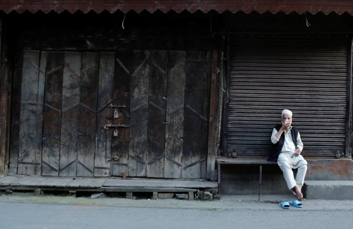 A Kashmiri man drinks tea as he sits outside closed shops. AFP file photo