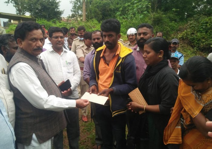 Virajpet legislator K G Bopaiah hands over a compensation cheque to the relatives of Leela, whose body was recovered in Thora on Thursday.