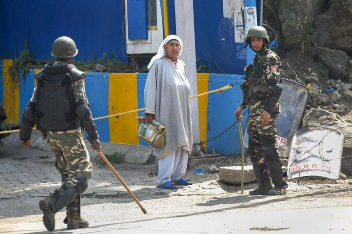An elderly woman seeks permission from security personnel during restrictions, in Srinagar, Friday, Aug. 23, 2019. (PTI)