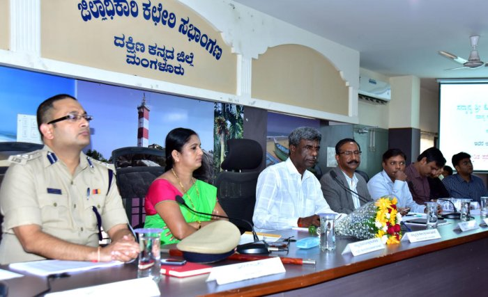 Minister Kota Srinivas Poojary conducts a review meeting at the DC's office in Mangaluru on Thursday.