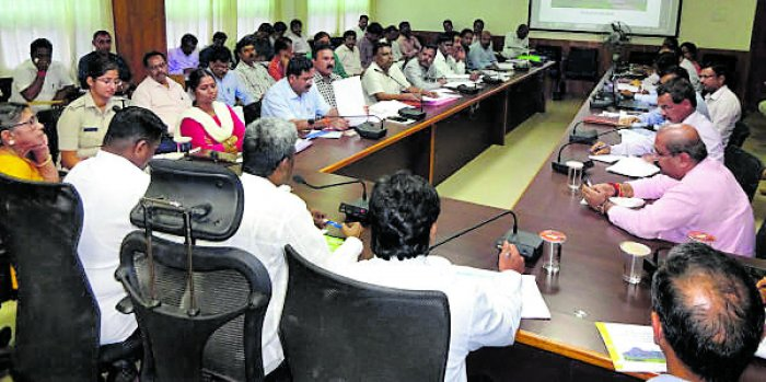 Minister Kota Srinivas Poojary attends a review meeting to take stock of flood relief work in Deputy Commissioner's office in Udupi on Thursday.