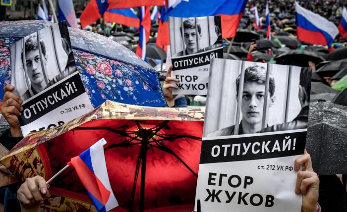 """Protesters hold posters reading """"Free (jailed student) Yegor Zhukov!"""" during a rally in central Moscow on August 10, 2019 after mass police detentions. (AFP Photo)"""