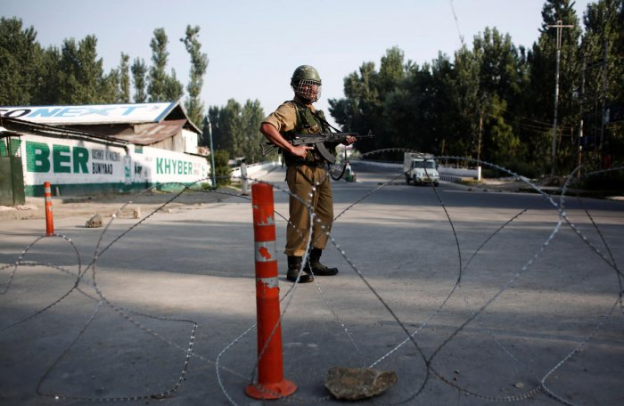 An Indian security personnel stands guard on a deserted road during restrictions after scrapping of the special constitutional status for Kashmir by the Indian government, in Srinagar. (Reuters Photo)