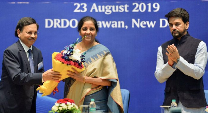 Finance Minister Nirmala Sitharaman is welcomed by Ashok Kumar Gupta, Chairperson of the Competition Commission of India (CCI) as MoS for Finance Anurag Thakur applauds during a function to celebrate 'Ten Years of Competition Law Enforcement' at DRDO Bhaw