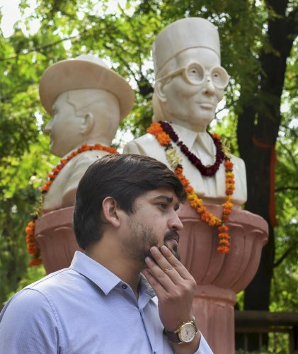 Delhi University Students' Union (DUSU) president Shakti Singh stands next to the busts of Veer Savarkar, Subhash Chandra Bose, and Bhagat Singh which were installed outside the Arts Faculty of the University, in New Delhi. (PTI Photo)