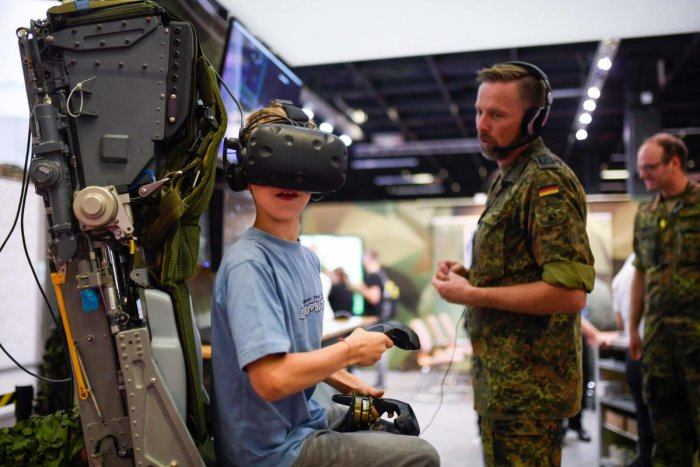 A boy visits the German Armed Forces Bundeswehr stand during the Video games trade fair Gamescom in Cologne, western Germany, on August 21, 2019. (Photo by Ina FASSBENDER / AFP)