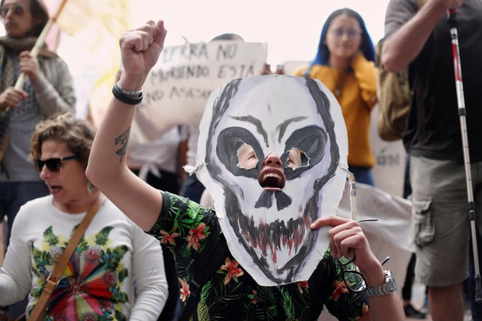 A demonstrator holds a paper mask in the shape of a skull during a protest to demand more Amazon rainforest protection at the embassy of Brazil in Quito, Ecuador August 23, 2019. REUTERS/Daniel Tapia