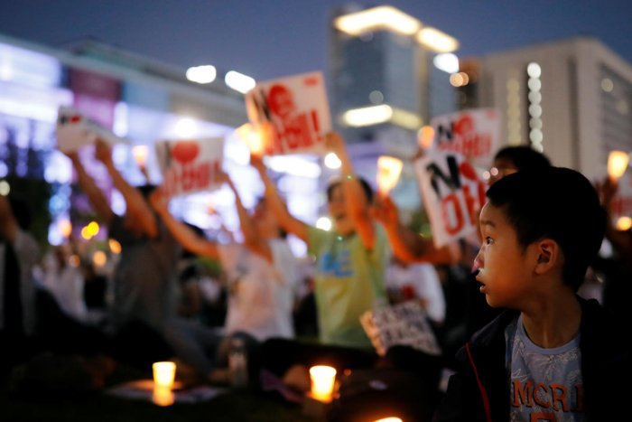A boy looks on as South Korean people chant slogans during an anti-Japan rally in Seoul. Reuters