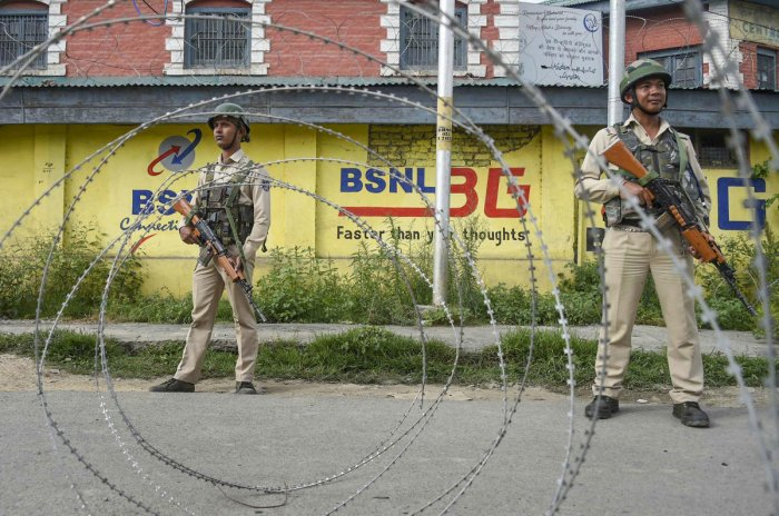 Srinagar: Security personnel stand guard near a blocked road during restrictions following the abrogation of the provisions of Article 370, in Srinagar, Friday, Aug 16, 2019. (PTI Photo)