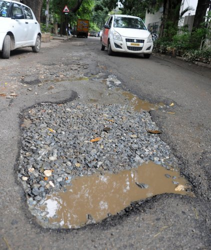 A pothole-ridden road in Indiranagar. (DH Photo)