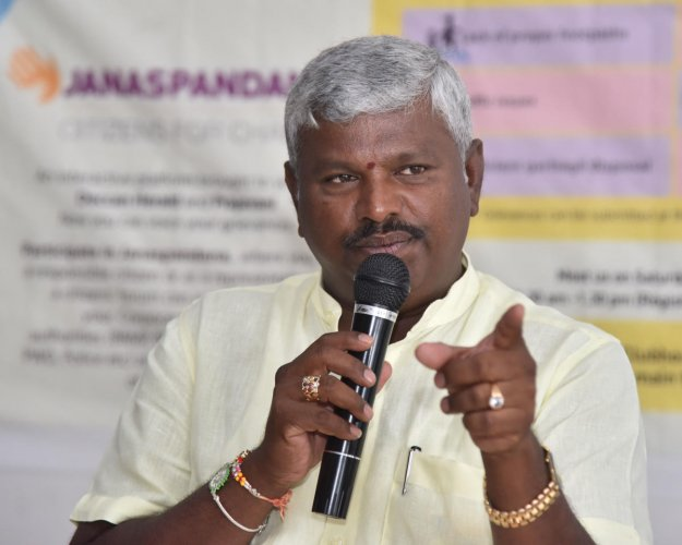 Begur corporator M Anjinappa speaks at Janaspandana, a civic grievance redress meet organised by DH and Prajavani, in Begur on Saturday. DH PHOTO/JANARDHAN B K