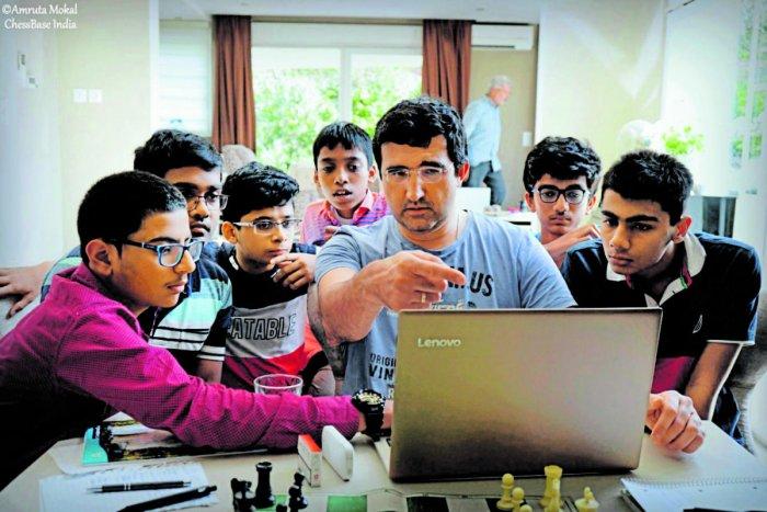 Chess legend Vladimir Kramnik (centre) explains a move to aspiring kids, part of Kramnik-Microsense programme, in Geneva.
