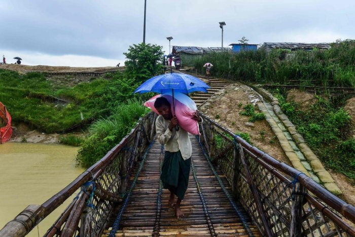 A Rohingya man shelters from the rain as he carries relief aid at the Kutupalong Rohingya refugee camp in Bangladesh's Ukhia district on August 24, 2019. (Photo by AFP)