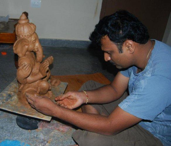 Chandrashekar G M working on a clay Ganesha sculpture.
