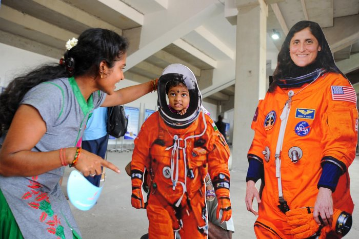 A woman helps her child wear spacesuit at a gallery at Satish Dhawan Space Centre, Sriharikota. Isro is bracing for India's first manned spaceflight. The Rs 10k-crore mission will see three-member crew blast off aboard Gaganyaan in Dec 2021. (DH File Photo)