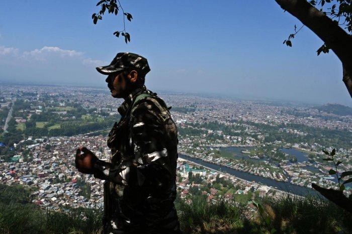 An Indian paramilitary trooper patrols at the top of a hill in Srinagar. (AFP Photo)