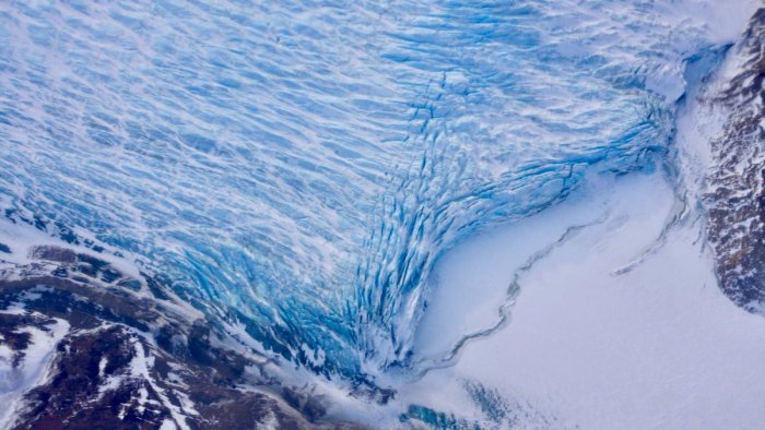 Cracks in the front of a glacier as it reaches the ocean. Credit: NASA/Adam Klein