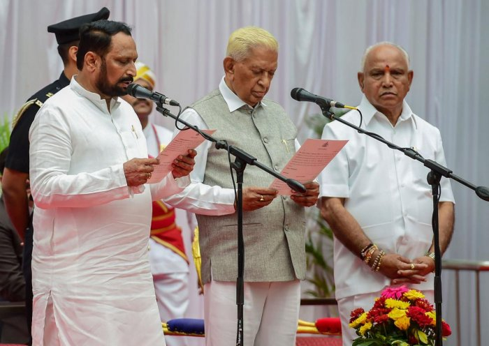 Karnataka Governor Vajubhai Vala administers the oath of office and secrecy to Laxman Savadi during the swearing-in ceremony of Karnataka BJP Government, at Raj Bhavan in Bengaluru, Tuesday, Aug. 20, 2019. (PTI Photo)