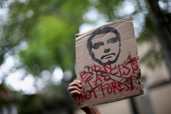 An activist holds a sign with an illustration of Brazilian President Jair Bolsonaro as they demand more Amazon rainforest protection at the embassy of Brazil in Mexico City, Mexico August 23, 2019. REUTERS/Edgard Garrido