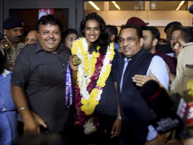 New Delhi: India's ace badminton player P.V Sindhu smiles as she arrives at T-3 terminal of IGI Airport after winning the BWF World Championship, in New Delhi. PTI