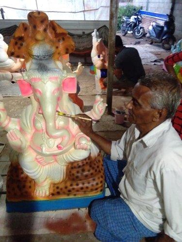 Kumbara Ishwarappa giving final touches to an idol of Ganesha in Tarikere.
