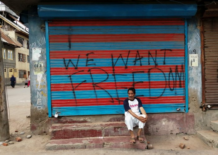 """a man sits next to graffiti that reads """"We Want Freedom"""" on a shuttered store in the Soura locality in Srinagar, during the lockdown. Photo by Jalees ANDRABI / AFP"""