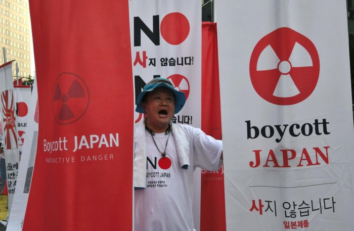 """A protester holding anti-Japanese banners during a rally against Japan's decision to remove South Korea from a so-called """"white list"""" of favoured export partners, near the Japanese embassy in Seoul. Photo/AFP"""