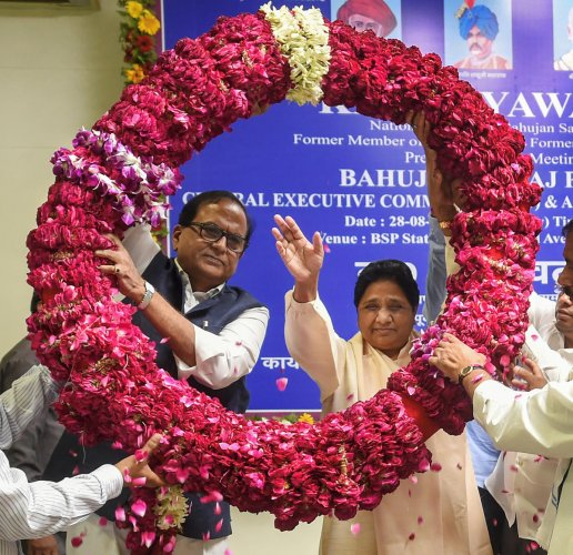 Bahujan Samaj Party (BSP) supremo Mayawati waves as she is garlanded by the party workers (PTI Photo)