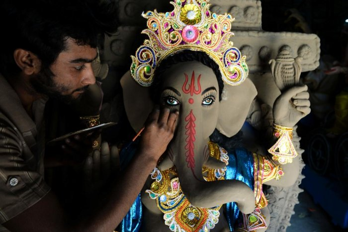 "An Indian artisan works on a sculpture of Hindu Lord Ganesh ahead of the upcoming ""Ganesh Chaturthi"" Hindu festival, at a workshop in Hyderabad. (AFP Photo)"