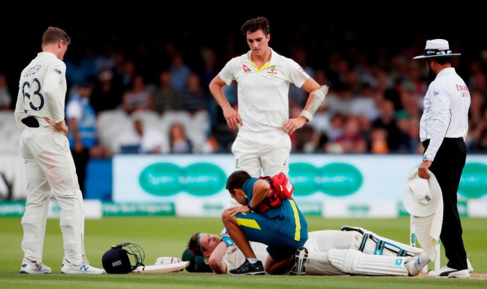 Australia's Steve Smith receives treatment as he lays on the floor after being hit by a ball from England's Jofra Archer as England's Jos Buttler and Australia's Pat Cummins. (Reuters Photo)