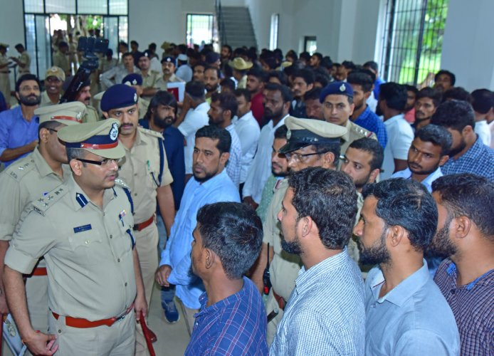 Commissioner of Police Dr P S Harsha interacts with people accused of being involved in rowdyism during parade at the police community hall in Mangaluru on Wednesday.