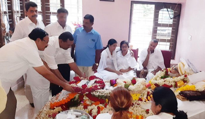 People pay homage to A K Subbaiah's mortal remains at his residence in Kallugundi coffee estate in Belluru near Gonikoppa on Wednesday.