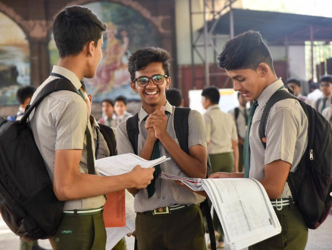 Students busy in last minute preparations for SSLC 1st day exam, before entering the exam hall, in Mysuru on Thursday. - PHOTO / SAVITHA B R